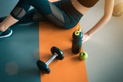 Fitness woman with Healthy workout equipment on gym floor. Exercise and Body build up concept. Beauty and sport theme. Relax and rest theme. Green apple and protein shake bottle and dumbbell in center