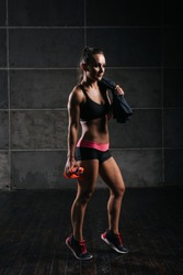 Fitness woman with perfect muscular body in black sportswear with towel on her shoulder, is holding bottled water in her hand on isolated black background. Sporty beautiful female is looking away