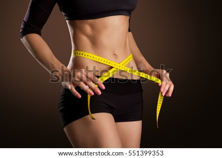 Fitness Woman With Tape Measure Showing Her Waist Isolated On Brown Background #551399353