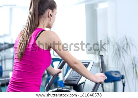Fitness Woman. Young sporty woman doing exercise on bicycle in the gym centre.