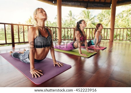 Fitness women practicing the cobra pose during yoga class in a health center. Fitness group doing cobra pose in row at the yoga class.
