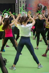 Fitness Workout at Gym: Exercises with Music and Green Drum Stick.