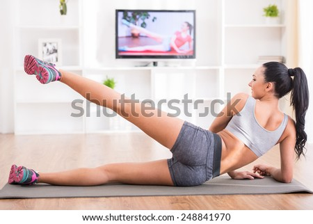 Fitness, workout, healthy living and diet concept.  Rear view of young woman is stretching on floor and watching tv at home.