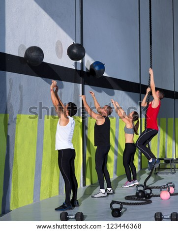 Fitness workout people group with wall balls and rope at fitness gym