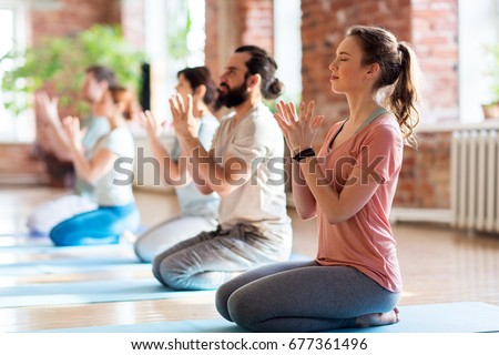fitness, yoga and healthy lifestyle concept - group of people doing lotus seal gesture and meditating in seated pose at studio