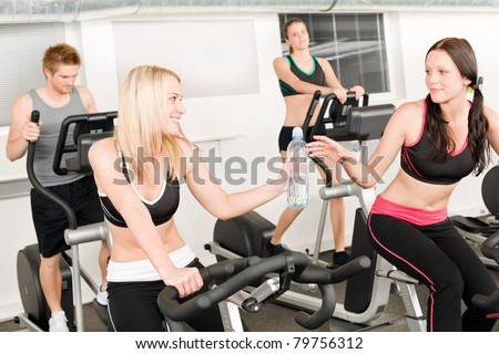 Fitness young girl on gym bike - crosstrainer in background