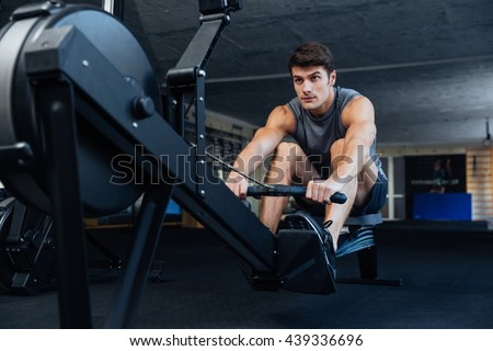 Fitness young man using rowing machine in the gym stock photo