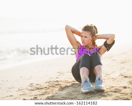Fitness young woman doing abdominal crunch on beach and looking on copy space
