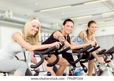 Fitness young woman on gym bike indoor cardio exercise