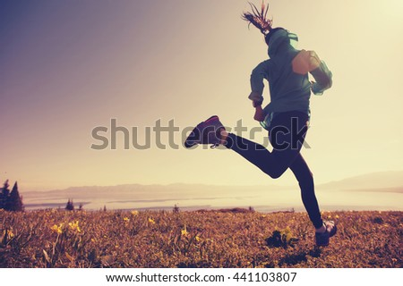 fitness young woman trail runner running on beautiful mountain peak #441103807