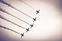 five aircraft flying in the sky with smoke behind