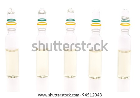 Five ampules with liquid medicine on white background