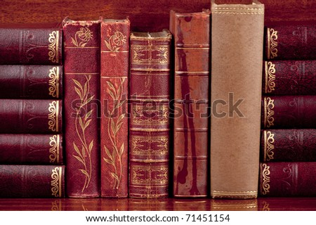 Five antique  books  standing up on a polished wooden shelf supported by other old books on their sides.