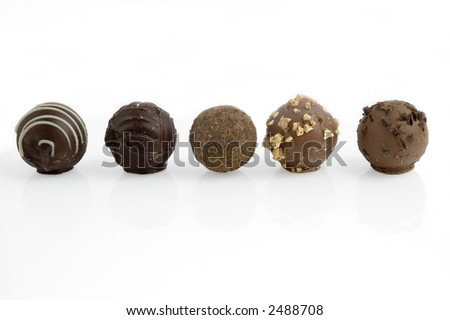Five assorted truffles in a row, isolated on white