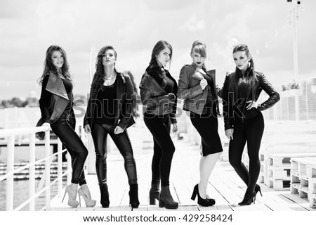 Five beautiful young girls models at leather jackets posing on berth. Black and white photo