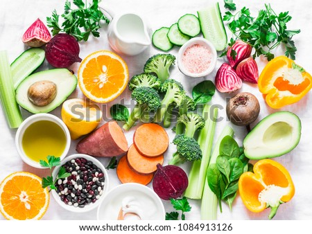 Five best vitamins for beautiful skin. Products with vitamins A, B, C, E, K - broccoli, sweet potatoes, orange, avocado, spinach, peppers, olive oil, dairy, beets, cucumber, beans. Flat lay, top view