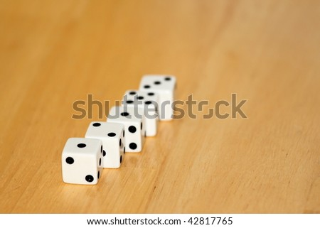 five black and white dice on a wooden background