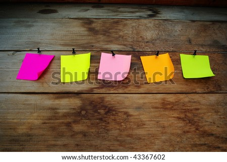 Five blank note papers attached to a wooden wall