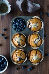 Five blueberry muffins in a muffin tin with one cup filled with blueberries.