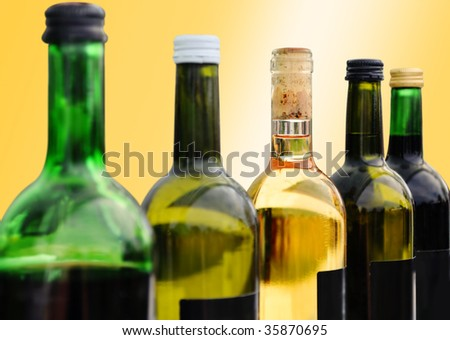 five bottles of different wine on a yellow background