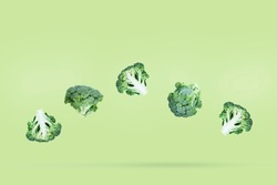Five broccoli soar freely on a green background with slight shadow. Creative flying food concept. Minimalist vegetable banner with copy space for text.