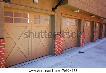 Five brown garage doors in perspective as part of an apartment complex
