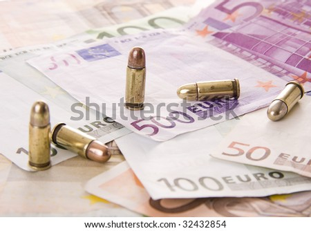 Five bullets and euro banknotes - Selective focus on the 500 euros