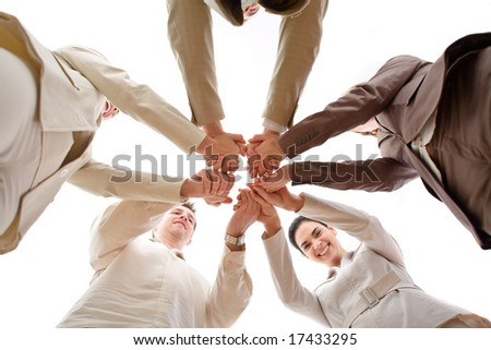 Five business people forming a circle and holding hands, smiling, low angle view.