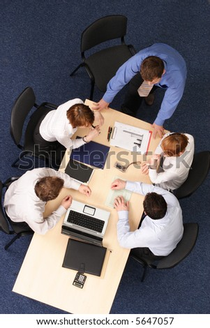 five business people meeting - boss speech .Businesspeople gathered around a table for a meeting, brainstorming. Aerial shot taken from directly above the table.