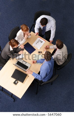 five business people meeting - boss speech,Businesspeople gathered around a table for a meeting, brainstorming. Aerial shot taken from directly above the table. - Shutterstock ID 5647060