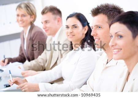 Five business people sitting in a row and writing notes on a business training. Selective focus placed on businessman in front. Browse my portfolio for vertical version.