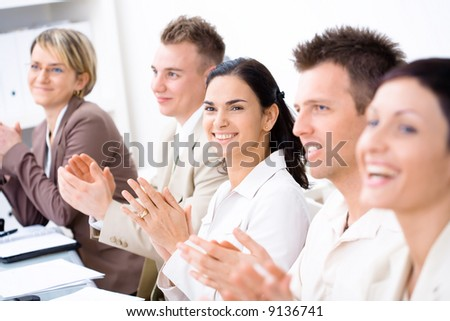 Five business people sitting in a row, smiling and clapping on business training. Selective focus placed on businesswoman in middle.