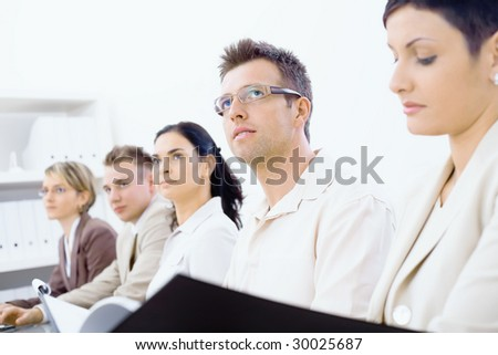Five businesspeople sitting in a row on a business training and paying attention, looking ahead. Selective focus placed on men in front