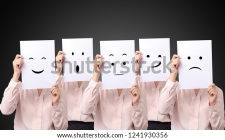 five businesswoman holding a card with drawing facial expressions different emotion feelings face on white paper #1241930356