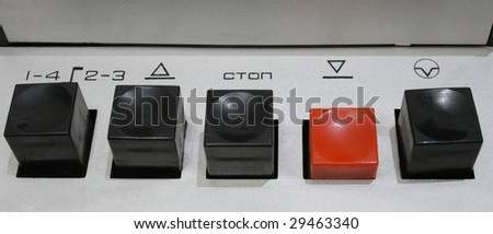 five buttons row of obsolete tape recorder. There are four black buttons and one red. Red button is pressed.