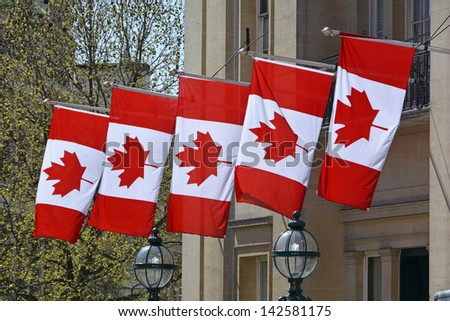 Five Canada national flags hanging from embassy building in Trafalgar Square London England UK