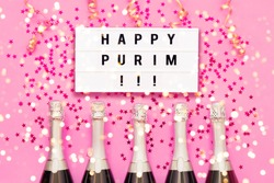 Five Champagne bottles with red confetti stars and Happy Purim written in light box on bright pink background. Purim celebration concept. Top view