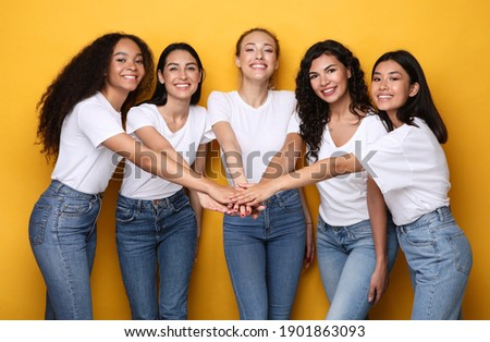 Five Cheerful Diverse Women Holding Hands Standing On Yellow Studio Background, Smiling To Camera. Female Unity And Friendship, Togetherness And Teamwork Concept Foto stock ©