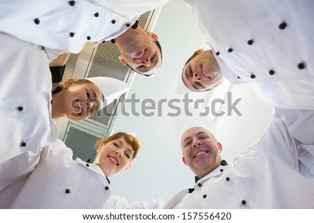 Five chefs standing in a circle wearing uniforms in a kitchen