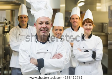 Five chefs wearing uniforms posing in a kitchen with crossed arms