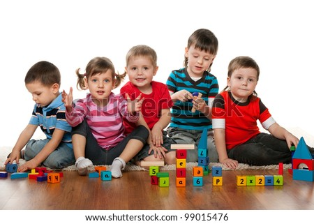 Five children are playing on the floor together