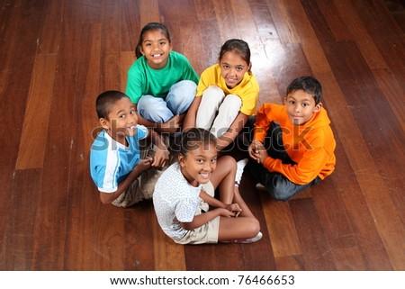 Five children sitting on classroom floor