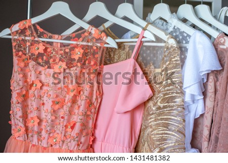 Five coloful dresses on white hangers. Pink dress. Gold dress. Coral dress on the hagers. #1431481382