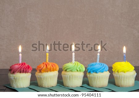 Five Colorful Cupcakes placed on green napkins with a lit candle on each. The cupcakes are on an antique table with a brown stucco background.