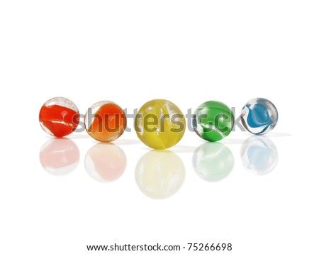 Five colorful marbles isolated and reflected on white