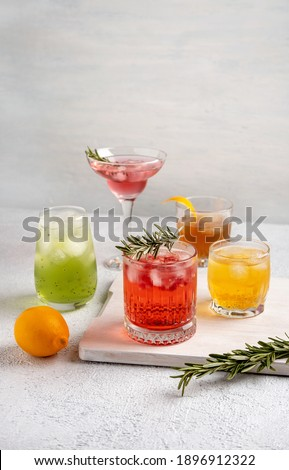 Five colorful summer cocktails in glasses on  white table. Assortment of fresh  summer drinks. Pink and red sangria cocktails, orange punch cocktail, margarita cocktail, tropical mule.