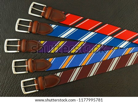 Five colorful web belts that have a collegiate stripe pattern on each of them. There are different colors, such as stripes in red and black, blue and white, purple and yellow, and more fun designs. #1177995781