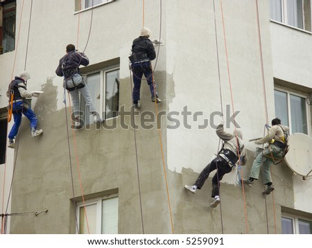 Five construction workers hanging on a rope from a tall building