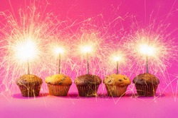 Five Cupcakes with a sparkler over a pink background - Birthday Concept