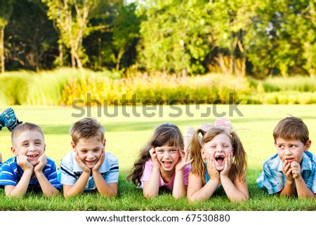 Five cute preschoolers laughing on the grass - stock photo